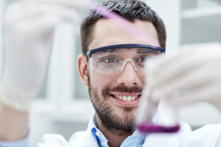 laboratory research: science, chemistry, technology, biology and people concept - young scientist mixing reagents from glass flasks and making test or research in clinical laboratory Stock Photo