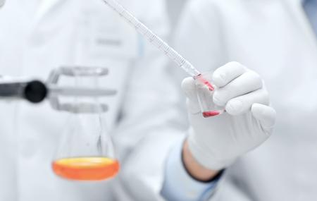 qu�mica: ciencia, qu�mica, la tecnolog�a, la biolog�a y la gente concepto - cerca de cient�ficos manos con la investigaci�n de llenado de la pipeta prueba fabricaci�n de tubos de laboratorio cl�nico