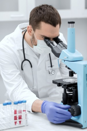 scientist man: science, medicine, technology, biology and people concept - young male scientist with test tubes looking to microscope and making or research in clinical laboratory