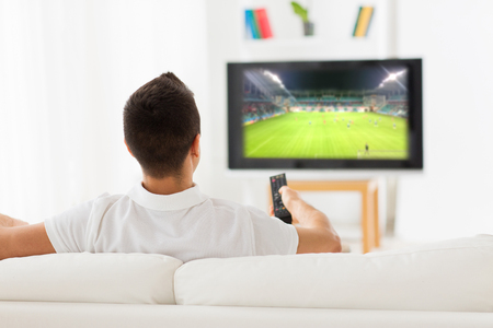 watching football: man watching football game on tv at home from back