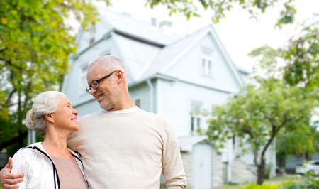 old home: happy senior couple hugging over living house background