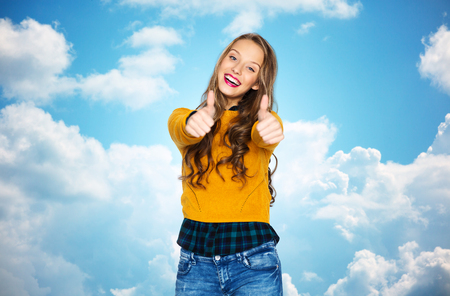 posing  agree: happy young woman or teen girl in casual clothes showing thumbs up over blue sky and clouds background