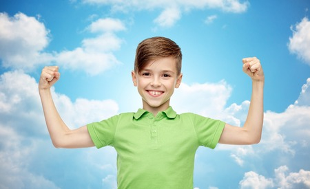 boy muscles: happy smiling boy in green polo t-shirt showing strong fists over blue sky and clouds background Stock Photo