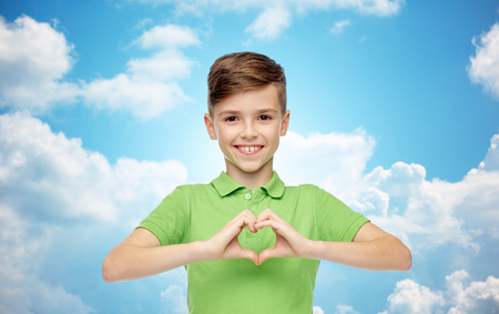 heart in hand: happy smiling boy in green polo t-shirt showing heart hand sign over blue sky and clouds background Stock Photo