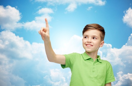 pre teen boys: happy smiling boy in green polo t-shirt pointing finger up over blue sky and clouds background Stock Photo