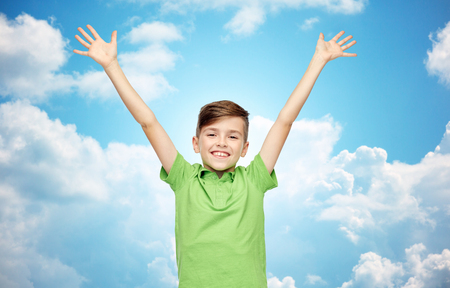pre teen boy: happy smiling boy in green polo t-shirt raising hands up over blue sky and clouds background