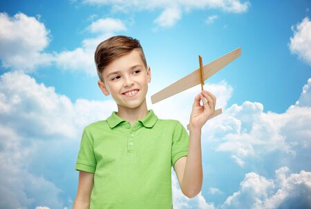 pre teen boys: happy smiling boy in green polo t-shirt with toy airplane over blue sky and clouds background