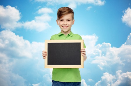 pre teen boys: happy smiling boy in green polo t-shirt holding black blank chalk board over blue sky and clouds background