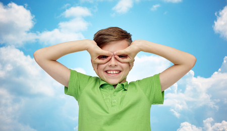 clouds making: happy smiling boy in green polo t-shirt having fun and making faces over blue sky and clouds background
