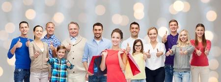 groep lachende mannen, vrouwen en kinderen tonen duimen omhoog en bedrijf boodschappentassen over vakantie steekt achtergrond aan