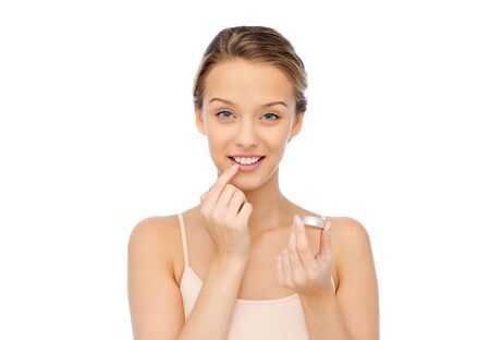 balm: smiling young woman applying lip balm to her lips Stock Photo