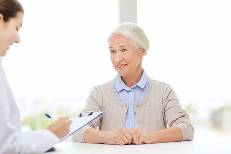 old people: doctor with clipboard writing prescription for senior woman at hospital Stock Photo