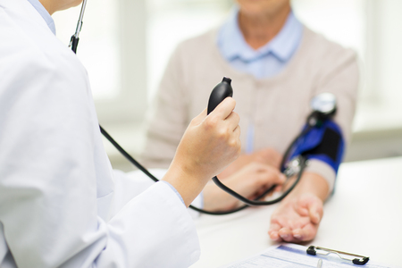 instrumental medico: cerca del doctor con el ton�metro de comprobar el nivel de presi�n arterial de la mujer mayor en el hospital