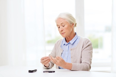 senior woman with glucometer checking blood sugar level at home Stock Photo