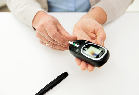 levels: close up of senior woman with glucometer and test stripe checking blood sugar level at home
