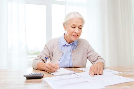 senior vrouw met papieren of rekeningen en rekenmachine schriftelijk thuis Stockfoto
