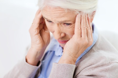 megrim: face of senior woman suffering from headache