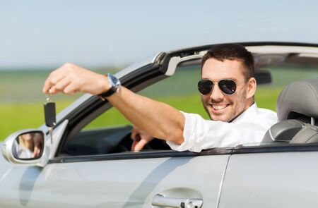 uomo felice in cabriolet mostrando chiave dell'automobile