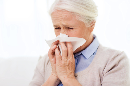 grippe: sick senior woman blowing nose to paper napkin at home