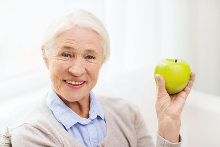 dental health: happy smiling senior woman with green apple at home Stock Photo