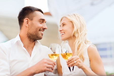 smiling couple clinking glasses of wine and looking to each other at restaurant lounge or terrace