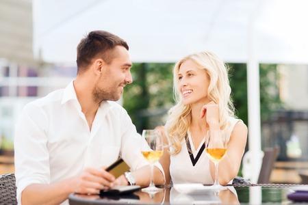 pagando: feliz pareja con gafas de tarjetas de crédito, facturas y el vino en la terraza del restaurante Foto de archivo