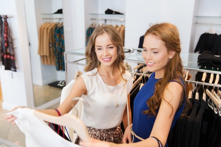 clothing shop: happy young women with shopping bags choosing clothes at clothing shop Stock Photo