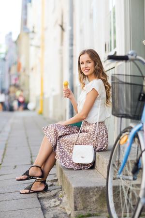 clavados: mujer inconformista joven feliz con la bici de pi��n fijo que come el helado en la calle de la ciudad