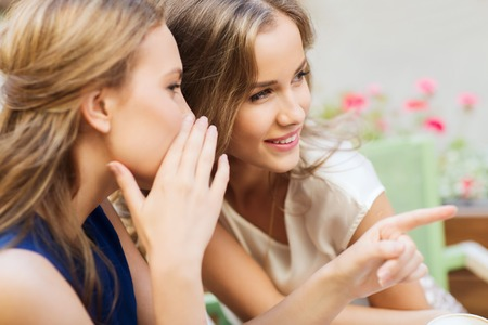 lächelnde junge Frauen am Café im Freien klatschend