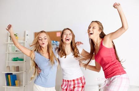 amistad: amigos felices o adolescentes que se divierten y que saltan en la cama en su casa Foto de archivo