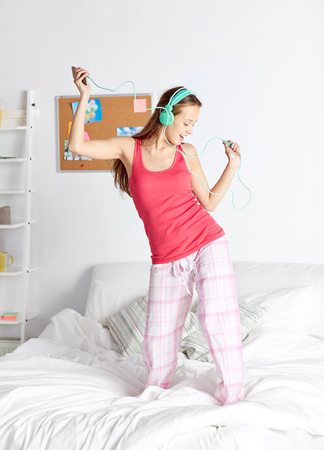 happy woman or teenage girl in headphones listening to music from smartphone and dancing on bed at home Foto de archivo
