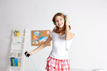 lovely woman: happy woman or teenage girl in headphones listening to music from smartphone and dancing on bed at home Stock Photo