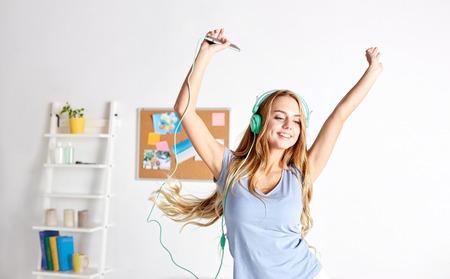 gl�ckliche Frau oder Teenager-M�dchen in den Kopfh�rern Musik vom Smartphone und Tanz auf dem Bett zu Hause h�ren