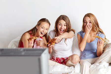 happy friends or teenage girls eating pizza and watching movie or tv series at home Standard-Bild