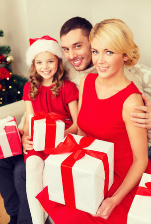 santa helper: smiling family in santa helper hats with many gift boxes