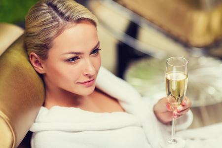 estilo de vida: jovem mulher bonita no branco roupão de banho deitado na chaise-longue e bebendo champanhe no spa