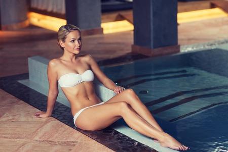 traje de bano: joven y bella mujer en traje de baño bikini sentada en el borde de la piscina de natación