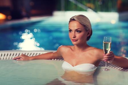生活方式: 美麗的年輕女子穿著比基尼泳裝在泳池邊的按摩浴缸與香檳玻璃坐