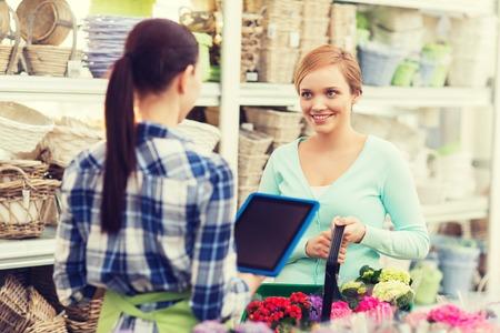 Giardiniere felice con tablet pc donna aiutando con i fiori che scelgono al negozio di fiori Archivio Fotografico - 51809783