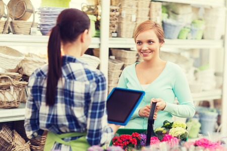 happy gardener with tablet pc helping woman with choosing flowers at flower shop