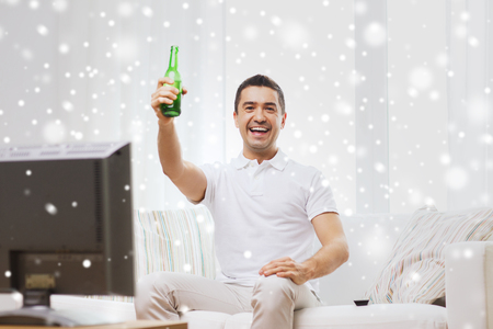 non alcoholic beer: smiling man with remote control watching tv and drinking beer at home over snow effect