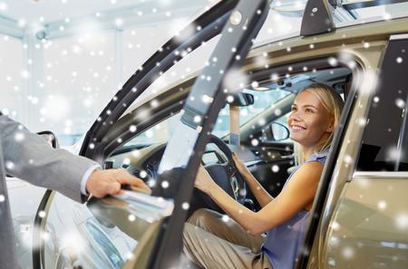 abriendo puerta: mujer feliz con el concesionario de coches en salón del automóvil o salón de más de efecto de nieve