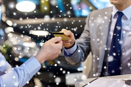 close up of customer giving credit card to car dealer in auto show or salon over snow effect