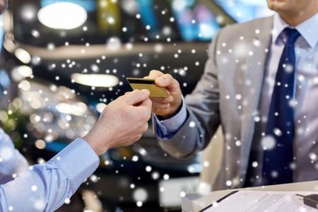 tarjeta de credito: de cerca de dar la tarjeta de crédito del cliente al concesionario de coches en salón del automóvil o salón de más de efecto de nieve