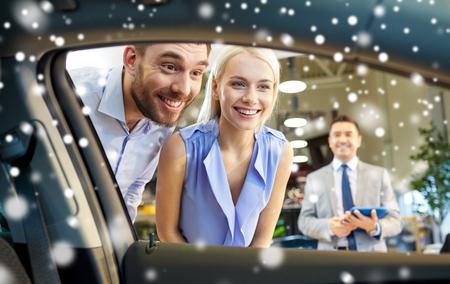 couple heureux regardant à l'intérieur voiture salon de l'auto ou un salon sur l'effet de la neige Banque d'images