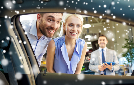 salesman: happy couple looking inside car in auto show or salon over snow effect