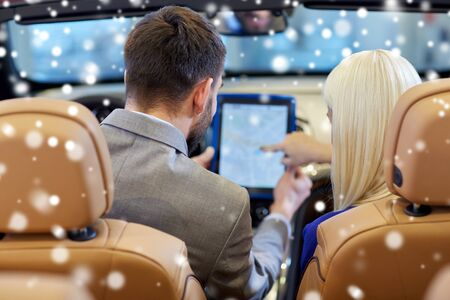 cabrio: close up of couple sitting in cabrio car with tablet pc computer at auto show or salon over snow effect from back