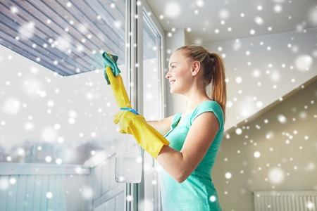 cleanser: happy woman in gloves cleaning window with rag and cleanser spray at home over snow effect