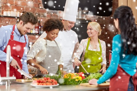happy group of friends and male chef cook cooking in kitchen over snow effect