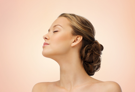 face side: young woman face with closed eyes and shoulders side view over beige background